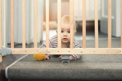 baby playing with ball behind safety gates