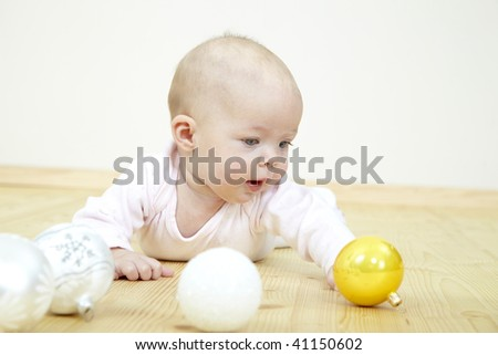 baby playing with christmas glitter balls