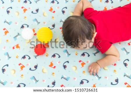 Baby playing with colorful toy rubber balls in the crib in a bright room. Child wearing a red bodysuit, laying on playful dinosaur crib sheet. #1510726631