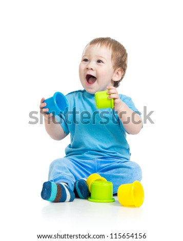baby playing with colourful cup toys on floor, isolated on white