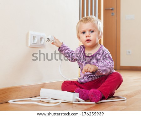 Baby playing with electrical extension and outlet on floor   #176255939