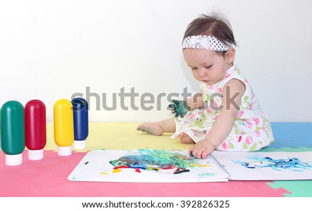 Baby playing with finger painting for early stimulation #392826325
