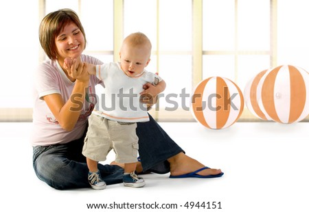 Baby playing with his mom. - stock photo