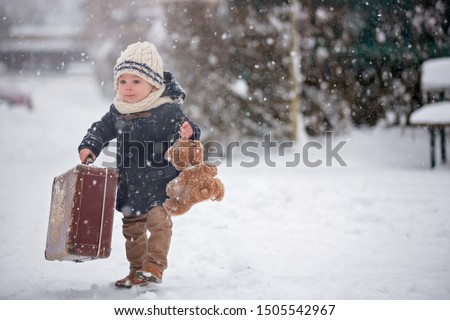 Baby playing with teddy in the snow, winter time. Little toddler boy in blue coat, holding suitcase and teddy bear, playing outdoors in winter park. Children play in snowy park
