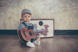 Baby playing with Ukulele.in vintage tone style