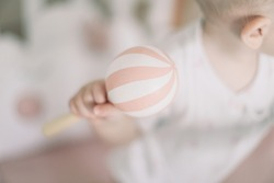 Baby playing with wooden toy. Kids hands holding a wooden baby rattle. Eco friendly non plastic toys concept. space for text. selective focus.
