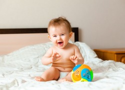 Baby plays with a multi-colored ball on the bed in the children's room