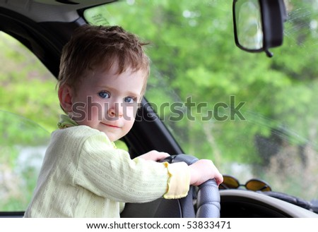 baby portrait holding steering wheel in car