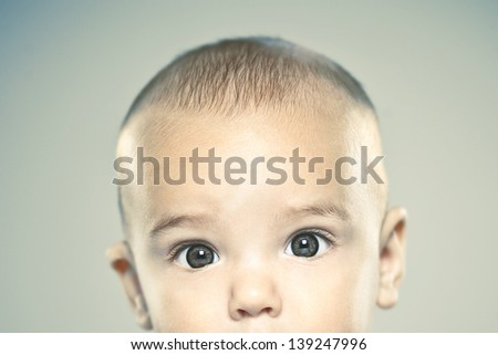 Baby portrait over grey background/ Adorable baby half face looking camera. Vintage style