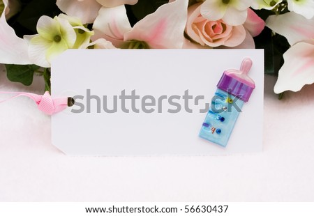 Baby present gift tag with a baby bottle and flowers in background, Welcoming a new baby