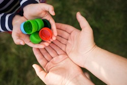 baby puts plastic lids in mother's hands. parent and his child collect cover. recyclable. collecting bottle caps.