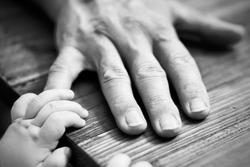 Baby reaches for Grandpa's hand