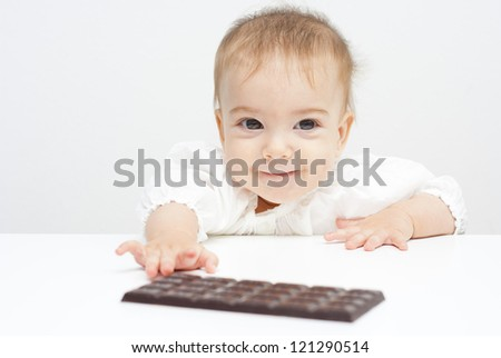 baby reaching chocolate bar