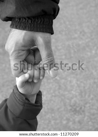 baby reaching up to hold on to father's finger, with space for text on the right side - stock photo
