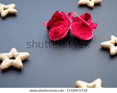 Baby red shoes on a dark grey background decorated with golden stars. Christmas winter theme. New baby announcement concept. Baby shower invitation. Baptism invitation idea. Flat lay top view.  Zdjęcia stock ©