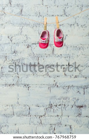 Baby red shoes on a rope against a white brick wall. #767968759