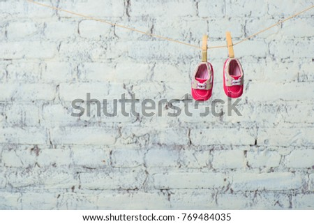 Baby red shoes on a rope against a white brick wall. #769484035