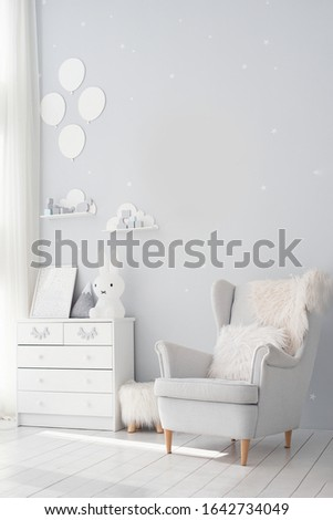 Baby room in scandinavian style. Stylish newborn playroom. Modern interior with grey walls and wooden accessories. Pastel grey monochrome decoration. Unisex nursery gender neutral. calm color palette.