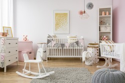 Baby room in scandinavian style with rocking horse, white cot