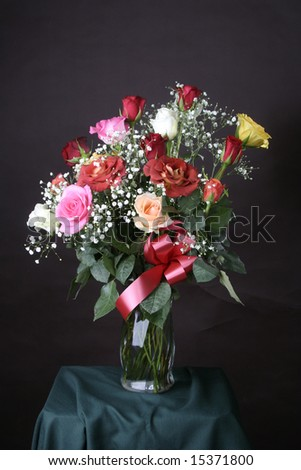 ... dozen roses in a floral arrangement set against a dark background