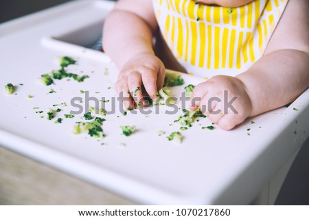 Baby's first solid food. Messy smiling baby eats and tastes with fingers vegetables broccoli in high chair. Healthy child nutrition. Mother gives to try foods to feed little child 7 months old Stock foto ©