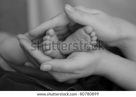 Baby's foot in mother hands.