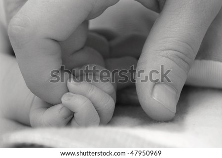 Baby's hand keeping adult finger