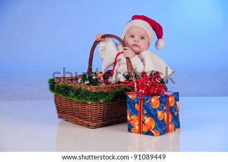 Baby Santa. Cute little girl dressed as Santa Claus sitting in a wicker basket with a gift. Basket decorated Christmas tree bells.