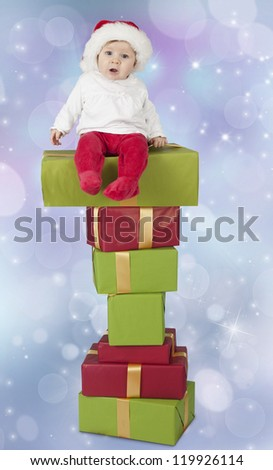 baby seated on a stack of christmas presents, blue bokeh background