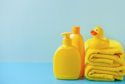 Baby shampoo or soap  on a blue  background, rubber yellow ducks and towel. Bathroom accessories