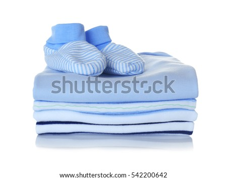 Baby shoes and pile of clothes on white background #542200642