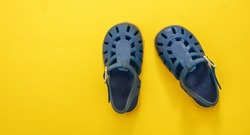 Baby shoes, beach sandals blue on yellow color background. Kids summer vacation footwear concept, top view.