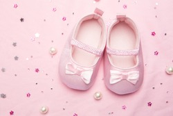 Baby shoes for a girl on pink blanket with pearls
