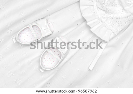 Baby shoes on an infant baptism dress