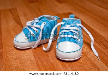 baby shoes. Pair of blue and white baby sneakers on the floor