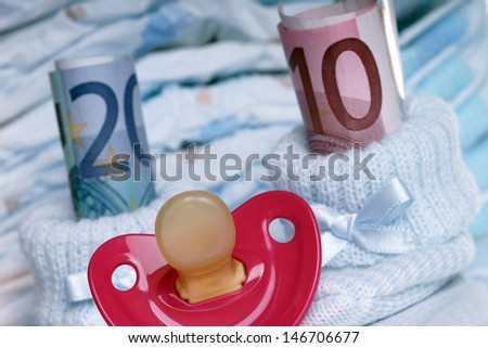 Baby shoes with baby teats and euro banknotes / Costs for a baby