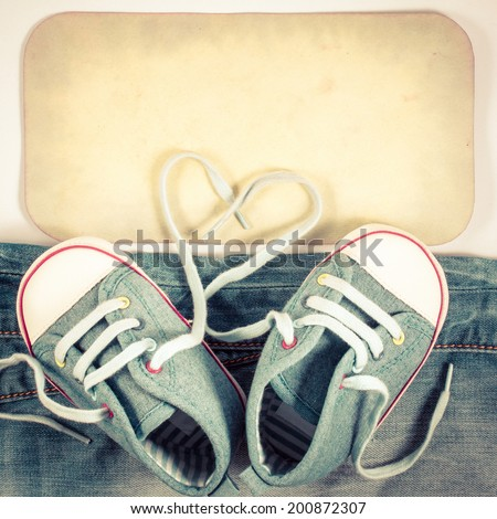Baby shoes with heart shaped lace on denim jeans and paper background. Retro style photo #200872307