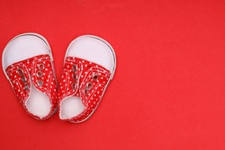 baby shoes with white polka dots on a red background