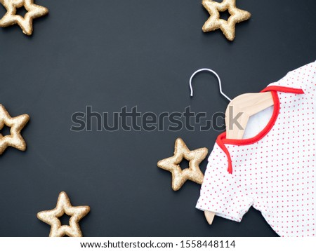 Baby shower concept with winter or Christmas theme. A white and red baby bodysuit on a dark background with golden stars. Baptism invitation. New baby birth announcement. Top view. Zdjęcia stock ©
