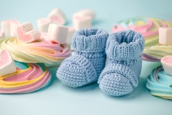 baby shower decoration - it is a girl. Rainbow sweetness and knitted blue booties socks on blue background. First birthday, newborn party
