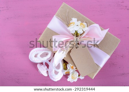 Baby shower Its a Girl natural wrap gift with gift box, baby booties and dummy on pink shabby chic rustic wood table.