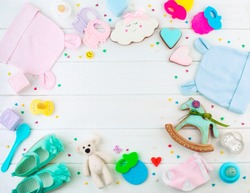 Baby shower party background: frame from baby clothes and accessories on white wooden background with copy space; top view, flat lay
