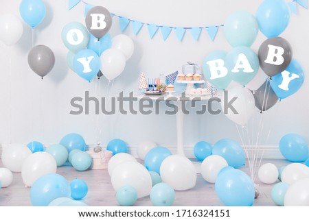 Baby shower party for boy. Tasty treats in room decorated with balloons
