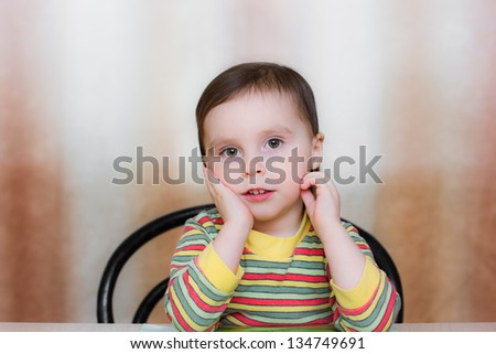 Baby sitting at the table and thinking. - stock photo