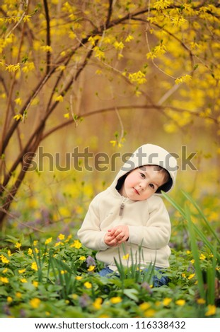 baby sitting by a beautiful bush with yellow flowers. spring