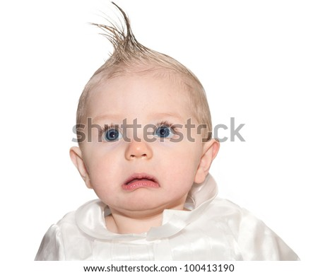 Baby sitting for a funny portrait with hair pushed into a fake mohawk and a frown