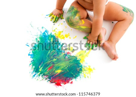 Baby sitting next to own painted color mosaic.Isolated on white.