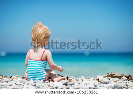Baby sitting on beach. Rear view - stock photo