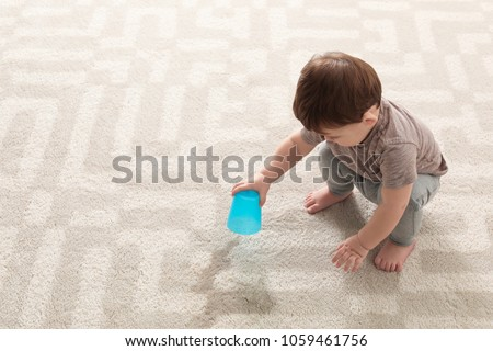 Baby sitting on carpet with empty glass