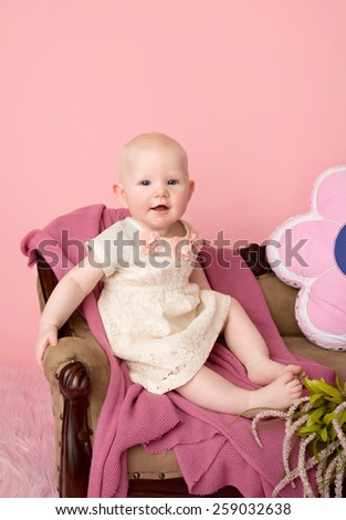 Baby sitting on couch with blanket, baby room and furniture concept